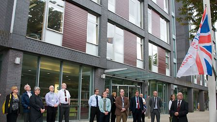 Council leader David Ellesmere raises the Armed Forces Flag at Grafton House watched by councillors