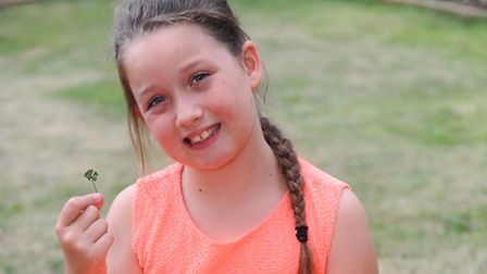 Nine-year-old Megan-Lucy Neville who has found a five-leaf clover in her garden in Ravenswood