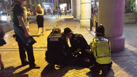 Officers detain a reveller in Ipswich town centre.
