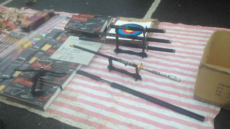 Crossbows and samurai swords on display at the car boot sale