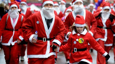 The EACH Ipswich Santa Run warms up on the Cornhill and then sets off on a damp and drizzly Sunday m