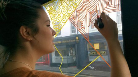 Artist Becky Whiting at work on her Pump and Grind window design