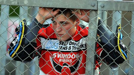Darryl Ritchings, pictured in Swindon Robins' colours, watches from the pits.
