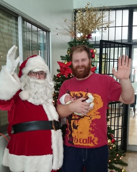 Proud dad Daniel Compton holding baby Evie meeting Father Christmas in the Dominican Republic