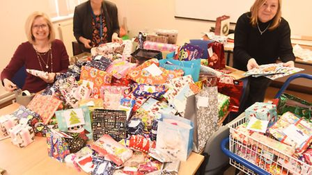 Ipswich Hospital charity Christmas elves wrap a mound of presents donated by staff and public before