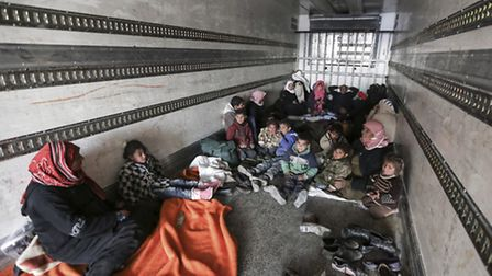 Syrians gather inside a truck to protect themselves from the cold weather at the Bab al-Salam border