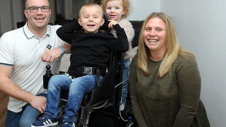 George Woodward is pictured with his new wheelchair at his home in Ipswich withLee Laura and sister