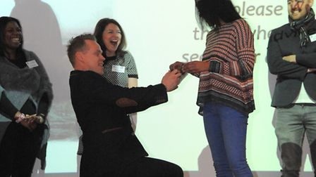 Paul Forde getting down on one knee to propose to Jeanelle Hume during an assembly at St Alban's Cat