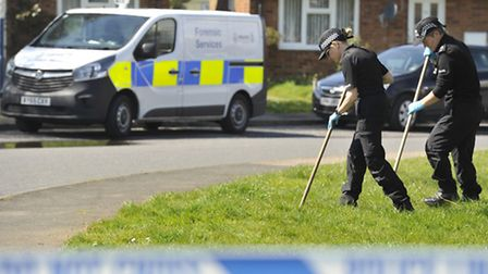 Police search the area around a home on Gosford Way where a woman's body was found.