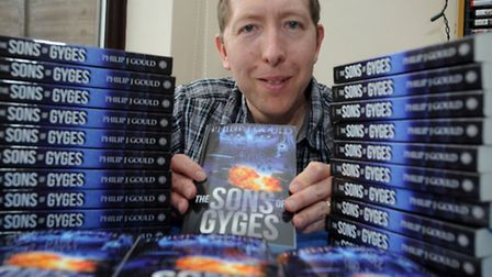 Philip Gould is pictured with his new book at his home in Ipswich.