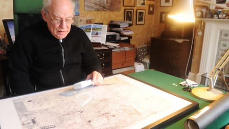 Mike cook with a copy of the 1958 plans for Ipswich's inner ring road