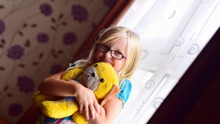 Hannah at home with her favourite bear.