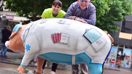 St Elizabeth Hospice's Samantha Catling and Pigs Gone Wild project manager Norman Lloyd with Dr Trot