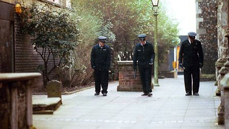 Police search the churchyard where Perry Wenham was murdered in January 1992