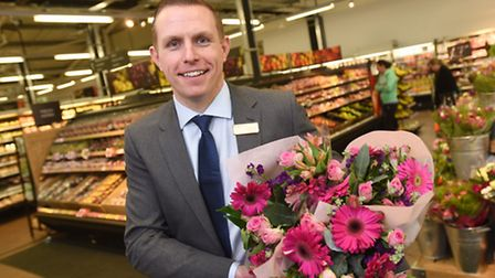 Store manager Ashley Mills shows off Mothers' Day flowers at the extended Marks and Spencer at Martl
