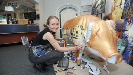 Lois Cordelia painting her Pig-geswyk at La Tour Cycle Cafe for for the Ipswich Pigs Gone Wild art t