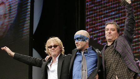 R.E.M. band members, from left, Mike Mills, Michael Stipe and Peter Buck wave as their leave the sta