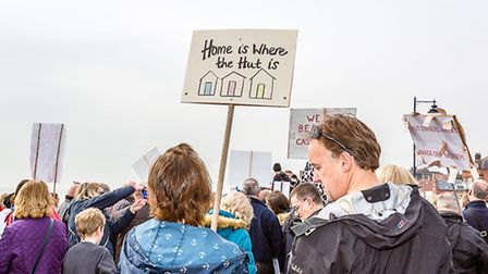 """Another creative sign says, """"home is where the hut is"""" at the Beach Hut Protest at Felixstowe on the"""