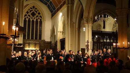 The St Mary-le-Tower choristers in their red cassocks and conductor Christopher Borrett with two bas