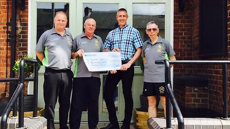 Rick Jones, Manager of Suffolk Seniors Over 50s hands the check to Simon Aalders watched by Steve Sm