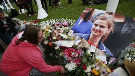 A woman laying down flowers of tribute at Parliament Square opposite the Palace of Westminster, cent