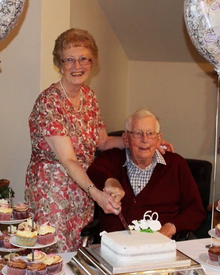 Margaret and Bryan Saunders cut the cake at their early anniversary party. Picture: CONTRIBUTED