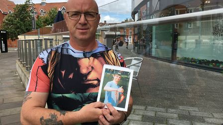 Richard Lungley holds a picture of his son Rhys, 20, at the site of the fatal crash. Richard was sho