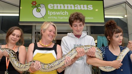 Emmaus staff get hands on with Buddy, an 18-foot python, from left, Abby Dezso, Claire and Jacob Sta