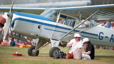 Resting beneath the wing of a plane whilst enjoying the races above