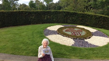 Lilian Caudle sitting in front of the East Suffolk Nurses' League's floral centenary tribute. Pictur