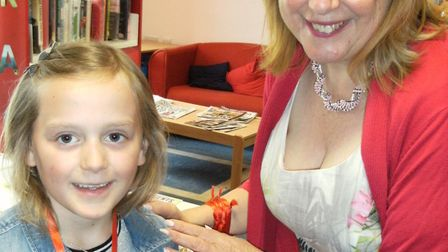 Iona receives her Summer Reading Challenge medal from Suffolk Libraries' chief executive Alison Whee