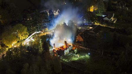 Firefighters tackling the thatched roof blaze at The Street, Rushmere St Andrew, on Tuesday night. P