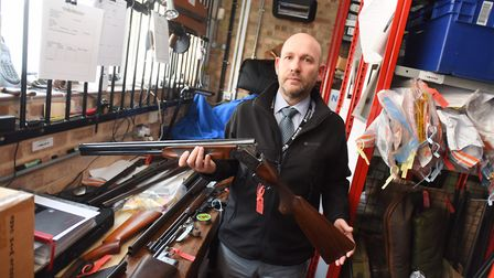 Richard Kennett with some of the firearms handed in on day one of a surrender campaign. Picture: ARC