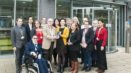 Portfolio holder for housing Neil MacDonald and staff from the department with their award outside G