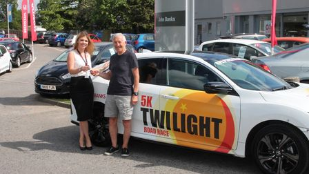 Representatives from John Banks handing over the lead Twilight 5k race car ahead of this weekend's e