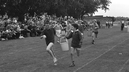Pupils race to get their bucket to the finish line first at Orwell High School's sports day in 1983.