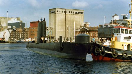 A visiting Royal Navy submarine turning in Ipswich with the assistance of a tug. Several submarines