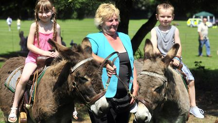 Kobi and Hollie Sparrow enjoying a donkey ride with Pat Symes of Cobwebs Donkeys during the 2011 L