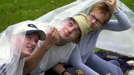 This trio shleters from the rain under a plastic sheet at Ipswich Music Day in 2000 Picture: ANDREW