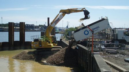 Diggers filling in the newly sculpted section of the west bank of the Ipswich tidal barrier defences
