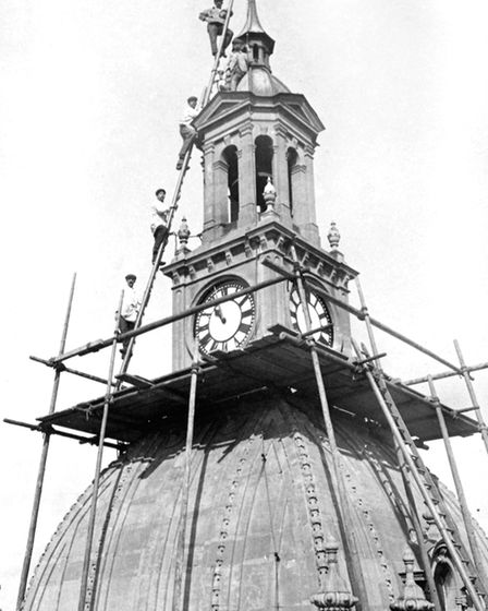 Workmen high on a ladder at the top of the Ipswich Town Hall early in the last century