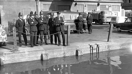 A group of police officers watch as the water at St Peters Dock, Ipswich, gets close to the edge of