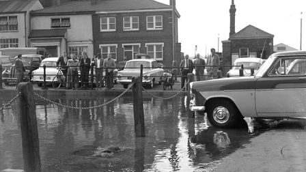 A group of men watching the water overflowing the Quay at St Peters Dock, Ipswich, in September 1969