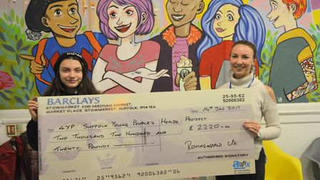 Teenage singer songwriter Roma Manteiga Nicholson hands over a cheque to Suffolk Young People's Heal