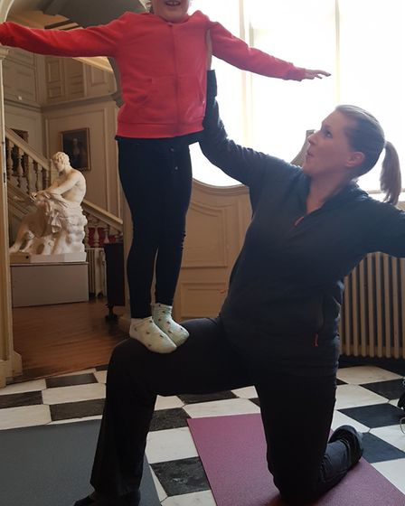 Five-year-old Daisy Ingram balancing on her mum Sarah during the family yoga session at Christchurch