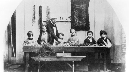 These Ragged School pupils appear to be making rag rugs under the watchful eye of teacher George New