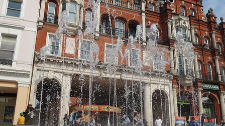 People enjoying the fountain on the Cornhill and sitting on deck chairs in the spring sunshine. Pic