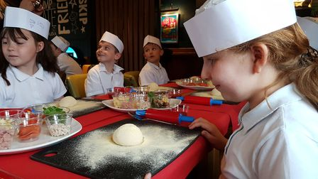 Pupils from Ravenswood Community Primary School spread their own pizza base in a healthy eating clas
