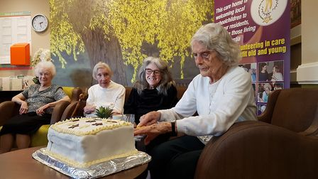 Care home resident Nora Velzian Burt celebrating her book publishing by cutting her cake. Picture: R