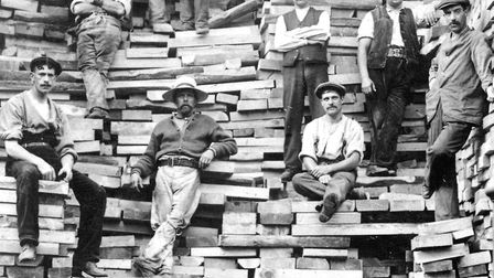 Workers with stacks of timber at the dock in the late 1920s. The wagon in the foreground belonged to